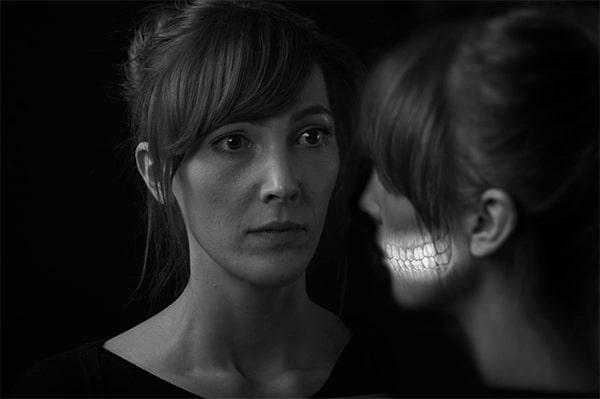 Parodontose bleibt meist unbemerkt, Frau vor Spiegel